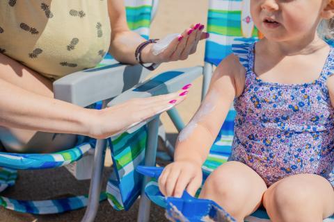 Niña con crema solar. Playa
